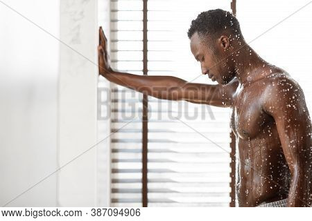 Muscular Black Man Taking Shower Washing Body Standing Under Water In Modern Bathroom At Home. Male