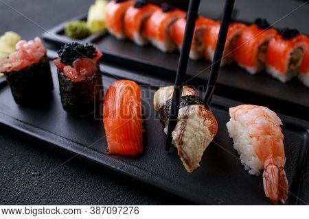 Eating Sushi. Chopsticks Taking Eel Nigiri Sushi From Plate. Japanese Food, Deluxe Restaurant Menu,
