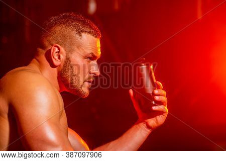 Young Man Drinks Water In The Gym. Man At Gym And Holding Bottle Of Water. Lifestyle Portrait Of Han