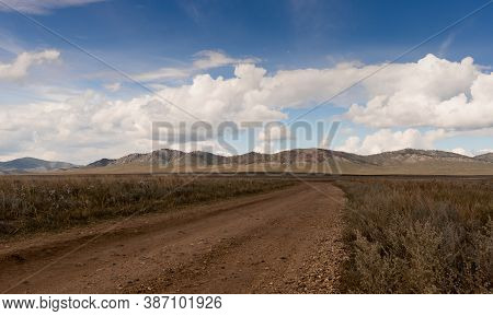 White Clouds In The Blue Sky Above The Steppe In Khakassia. Wide Dirt Road Going Through The Steppe