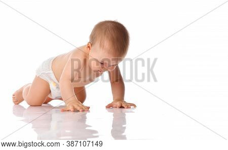 Young Baby Explorer In Diaper Crawling On Studio Floor Isolated On White Background. Little Toddler
