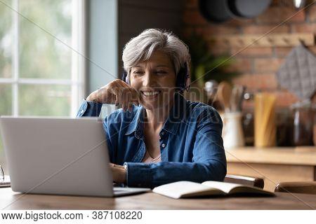 Smart Elderly Woman In Headphones Watch Webinar On Laptop