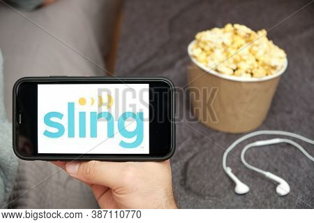Sling Logo On The Smartphone Screen With Popcorn Box And Apple Earpods On The Background, September
