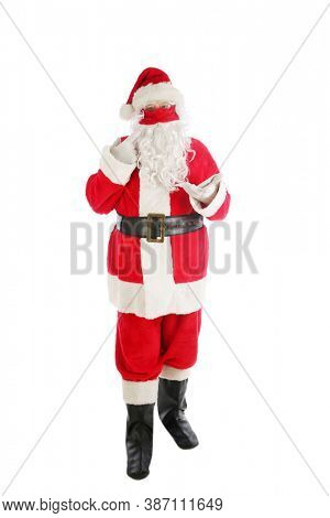 Santa Claus Coronavirus Christmas. Santa Claus stands and wears his Red Velvet Face Mask to avoid contacting Covid-19. Wear your mask. Full Body Shot of Santa Standing. Merry Christmas to all.