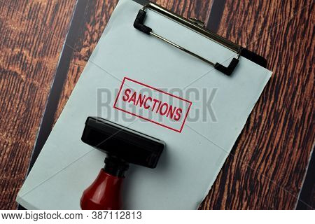 Close Up Red Handle Rubber Stamper And Text Sanctions Isolated On White Background.