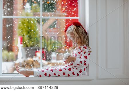 Young Pretty Girl With Blond Curly Hair And Red Christmas Bow In White Winter Pyjamas Sitting Near T