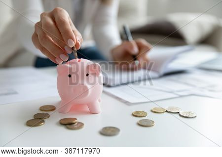 Close Up Of Woman Put Coin In Piggybank Saving