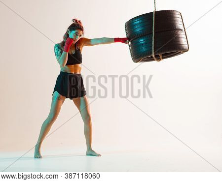 Cool Female Fighter Trains Jab On Beige Background In Neon Light. Womens Sport And Motivation Concep