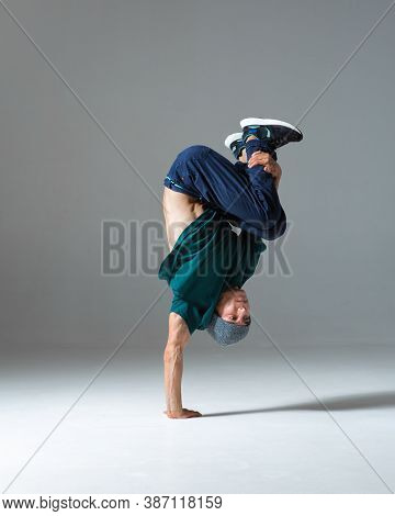 Cool Guy Breakdancer Stands On One Hand Dancing Lower Break Dance Isolated On Gray Background. Break