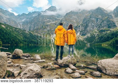 Man With Woman In Yellow Raincoat At Sunny Autumn Day Looking At Lake In Tatra Mountains