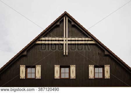 Gable Roof Of Cottage With Cloudy Sky In Background.there Are 3 Glass Windows With Wooden Decorated