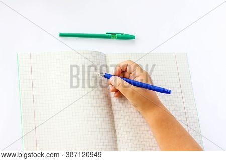 The Child Holds His Hands Over An Open Notebook And Is Going To Write In It. Close-up Of A Child's H