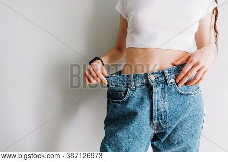 Slimming Concept. Young Woman Holds Jeans In Her Hand, Shows A Thin Waist Slim Female Body In Large