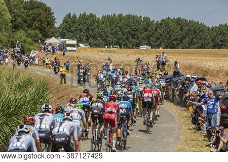 Escaudoeuvres, France - July 15 , 2018: Rear View Of The Peloton Riding On A Cobblestone Road During