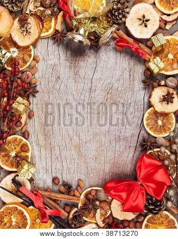 Christmas spices with dry orange and apple slices in frame with free space for text