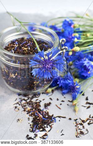 Black Tea Mix With Dried Cornflower Petals And Thyme In Glass Jar With Fresh Cornflowers.
