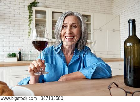 Happy 60s Mature Woman Drinking Wine Video Calling Friend At Home. Old Middle Aged Lady Holding Glas