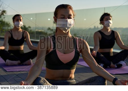 Fit Sporty Young Woman Wear Medical Face Mask For Safety Meditating Keeping Social Distance With Fem