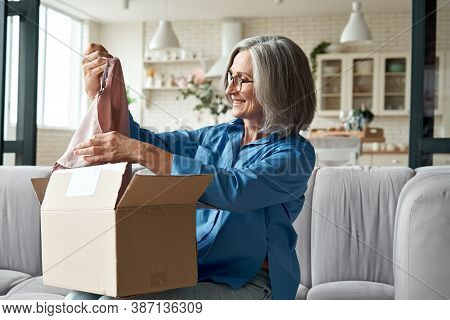 Happy Middle Aged Woman Buyer Opening Parcel Box At Home. Smiling Old Mature Female Customer Shopper