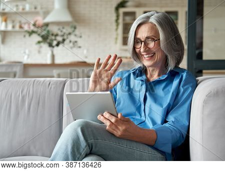 Happy 60s Older Mature Middle Aged Adult Woman Waving Hand Holding Digital Tablet Computer Video Con