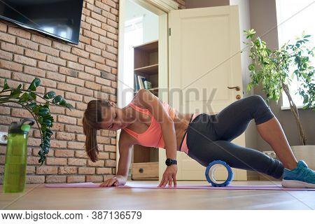 Fit Sporty Woman Wearing Sportswear Roll On Foam Massage Roller Massaging Leg Muscle Lying On Yoga M