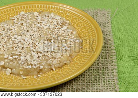 Mashed Banana With Oats On Yellow Plate