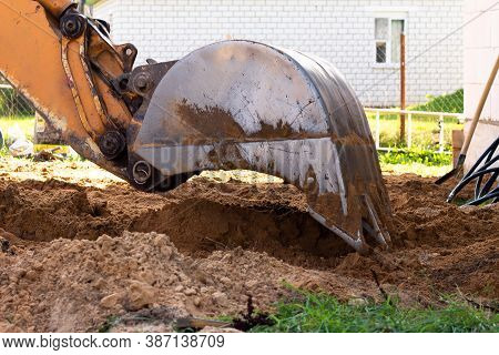 An Excavator Metal Bucket Digs Sand Or Clay On A Construction Site While Digging A Trench.