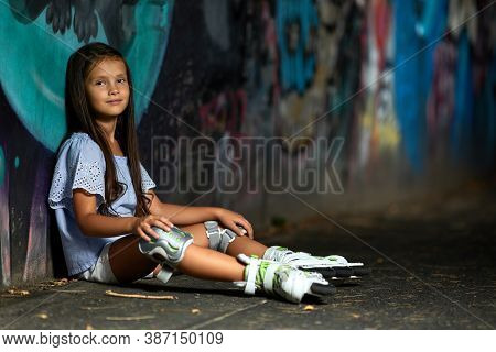 Happy Tired Little Child Girl In Roller Skates Is Resting After Rollerskating In Park In The Evening