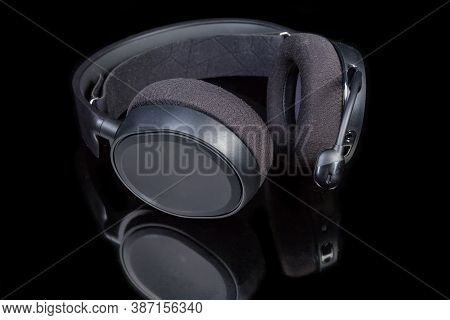 Black High-fidelity Headset With Earpads Circumaural Type And Microphone On A Dark Reflective Surfac