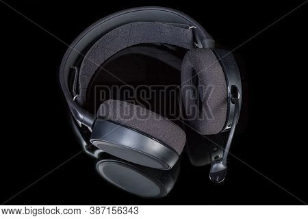 Black High-fidelity Headset With Earpads Of Circumaural Type And Microphone On A Dark Reflective Sur