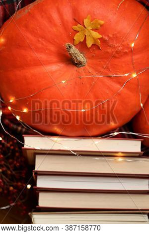 World Book Day. Autumn Books.reading Concept.halloween Books.a Large Orange Pumpkin With Glowing Gar