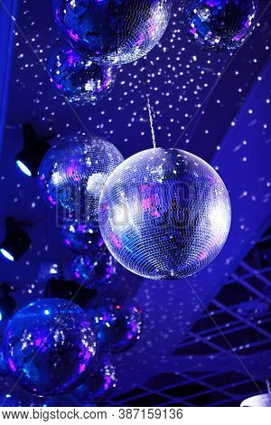 Light And Music Disco Ball On A Blue Background. A Rotating Disco Ball In A Nightclub With Sparkling