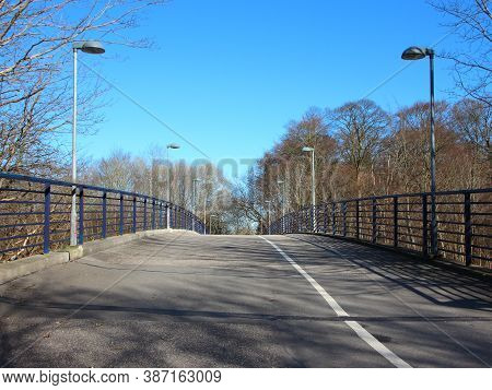 An Empty Curved Pedestrian And Bicycle Crossing Road. It Is A Bridge With Lampposts On Either Side.