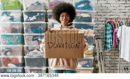 African American Girl Holding Donation Box And Looking At Camera, Posing In Front Of Boxes Full Of C