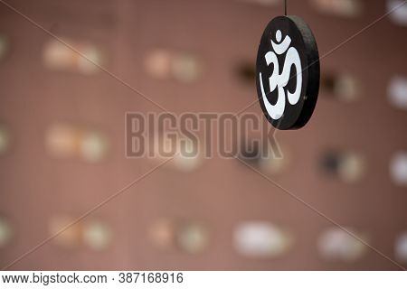 Hindu Symbol Om Painted White Hanging On A Circular Piece Of Wood Painted Black In A House