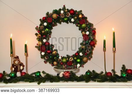 Above The Fireplace Hangs A Wreath Of Spruce. Christmas Wreath Over Fireplace Mantel. Place For Text