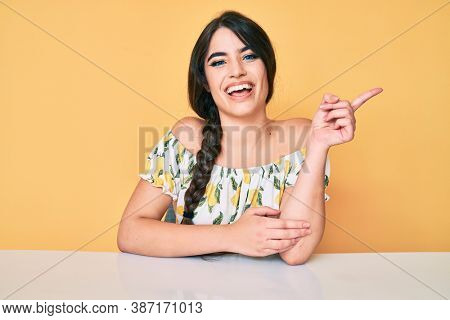 Brunette teenager girl wearing casual clothes sitting on the table with a big smile on face, pointing with hand and finger to the side looking at the camera.