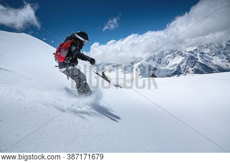 Girl Snowboarder With A Backpack On A Snowy Fresh Slope Against The Backdrop Of High Mountains And B