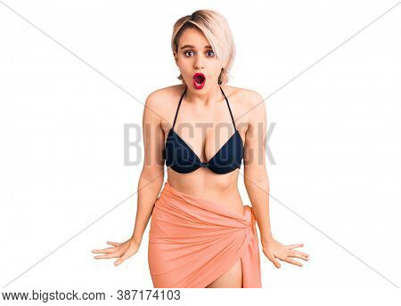 Young beautiful blonde woman wearing bikini scared and amazed with open mouth for surprise, disbelief face