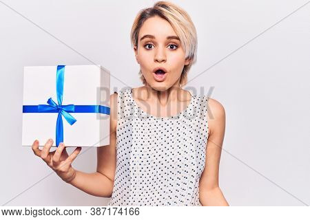 Young beautiful blonde woman holding gift scared and amazed with open mouth for surprise, disbelief face