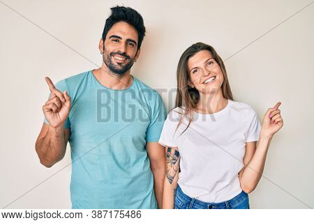 Beautiful young couple of boyfriend and girlfriend together with a big smile on face, pointing with hand finger to the side looking at the camera.