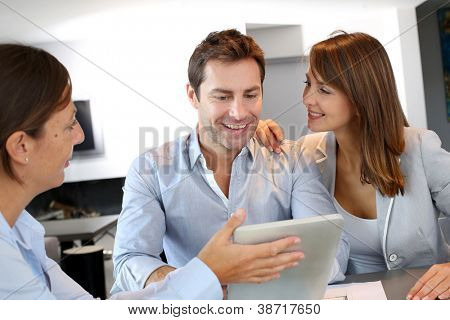 Couple meeting architect for plans of future home poster