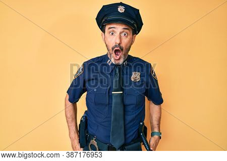 Middle age hispanic man wearing police uniform afraid and shocked with surprise and amazed expression, fear and excited face.
