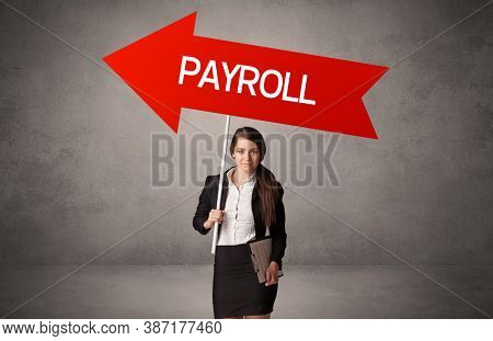 Young business person in casual holding road sign with PAYROLL inscription, business direction concept