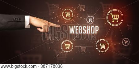 Close-Up of cropped hand pointing at WEBSHOP inscription, online shopping concept