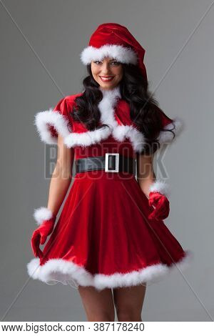 People, holidays, christmas and celebration concept - beautiful sexy woman in santa hat and red dress on gray background