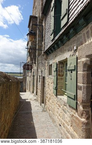 Mont St Michel, France: July 2020; Narrow Alleyway In The Old Town Of Mont St Michel With A Hanging