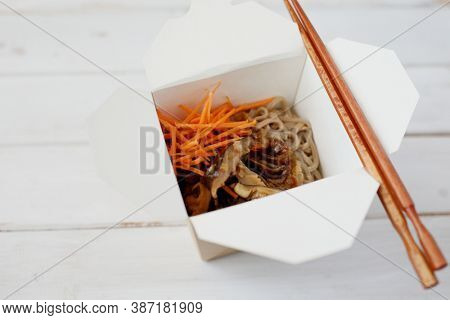 Shiitake mushrooms and soba noodles with carrot in a disposable wok box