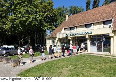 Issigeac, France: July 2020: Customers Queuing To Withdraw Cash From A Cashpoint At A Branch Of The