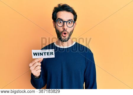 Young hispanic man wearing glasses holding winter word on paper scared and amazed with open mouth for surprise, disbelief face